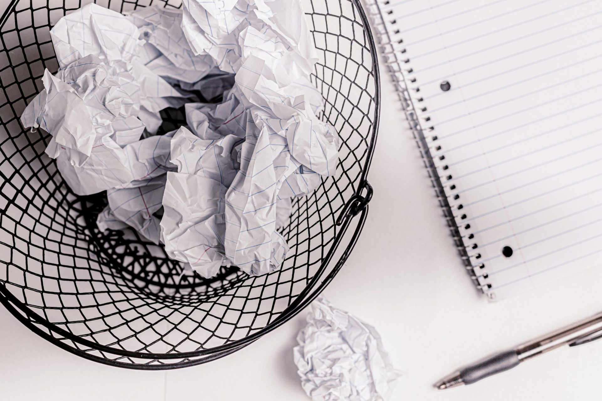 Black wire wastepaper basket with crumpled paper next to a notebook, ball of paper, and pen with a white background